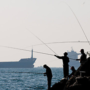Men fish on the coast of Taejongdae, a natural park in the port city of Busan, South Korea.
