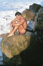 sexy man in a speedo sitting on a rock formation in Malibu, CA