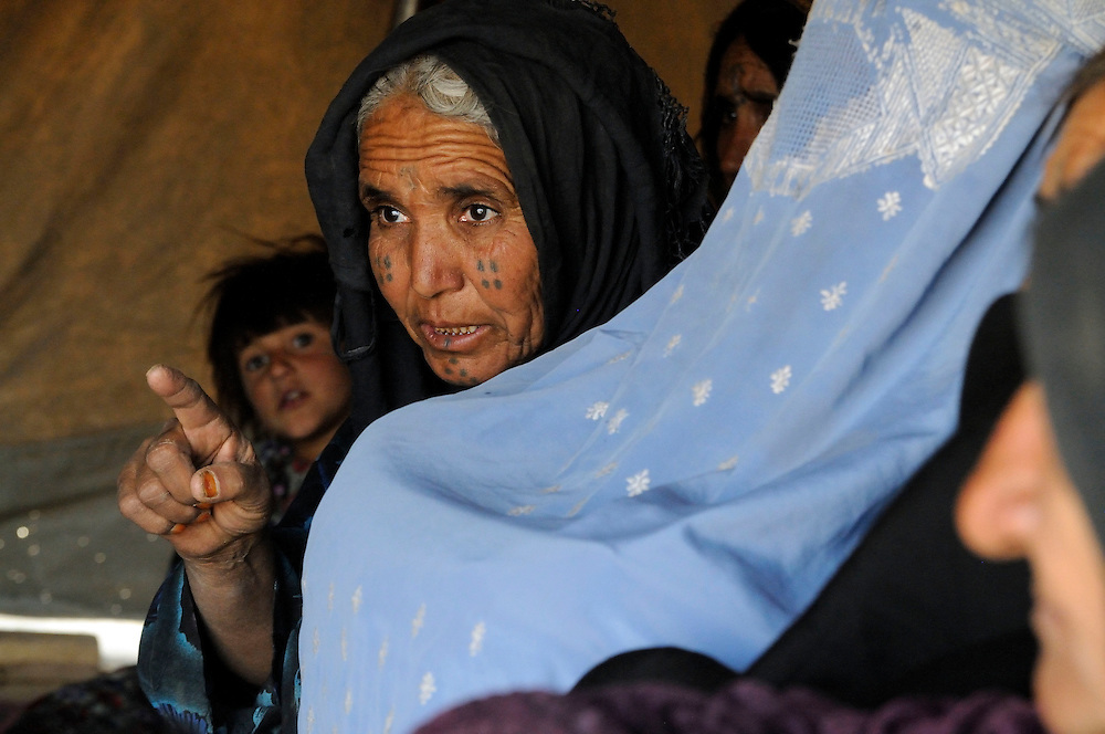 UNHCR returnees speak with Mr. Adel and Vivian Tan from UNHCR at Mohajir Qeshlaq, Sholgara District, Balkh Province, Afghanistan, on Monday, October 6, 2008.  Mr. Abdul Qayum's family faces desperate conditions with winter coming, unable to build a home due to unresolved land issues. His oldest son Akhtar, age 15, like many young men is returning to Pakistan for work.  His other children, Hakim age 11 and Mastura, age 9, are laboring in the cornfields attempting to feed their family.   His younger children include Aziza and Manam, with wife Shah Bibi, a widowed relative and the family's Grandmother...Background:  In early summer 2008, around 150 families returned to Sholgara district from Jalozai camp in Pakistan. They had acquired a piece of land before return, but due to ethnic tension the surrounding communities fiercely opposed the settlement of Pashtuns in their midst. For 4 months they lived in a camp-like situation in Sholgara centre but now the government has identified a piece of land for them in Mohajir Qeshlaq. This year UNHCR was unable to include them in its shelter program due to the unsettled land issue, but they are expected to be included in the 2009 shelter program.  .