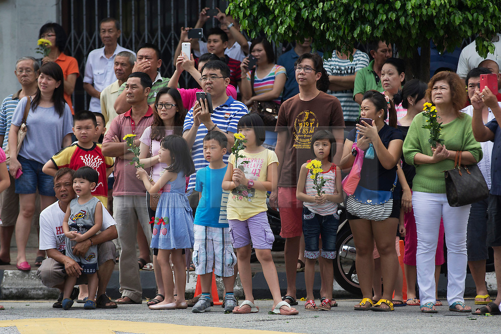 © Licensed to London News Pictures. 28/09/2014. Ipoh, Malaysia. People watch a procession of devotees with deities through the streets of central Ipoh, Malaysia on the 5th day of the Nine Emperor Gods Festival, Sunday, Sept. 28, 2014. The festival is a nine-day Taoist celebration to mark the birth of the Nine Emperor Gods from the first day to the ninth day of the ninth moon in Chinese Lunar Calender. The origin of the Nine Emperor Gods (stars of the Northern constellation) can be traced back to the Taoist worship of the Northern constellation during Qin and Han Dynasty and absorb this practice of worshipping the stars and began to deitify them as Gods. Photo credit : Sang Tan/LNP