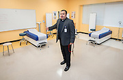 Hartman Middle School principal Geovanny Ponce shows off the clinical classroom during the dedication of the school's Health and Medical wing, April 3, 2014.