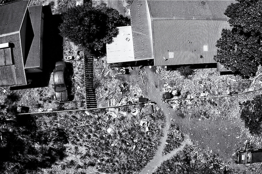 An aerial view of two condemned houses in Kennedy Hill. The left house was demolished on September 19th and the right house September 22nd. The area under the right tree and around the abounded car has now become a bush camp. A lack of affordable short-term accommodation, combined with Aboriginal people moving in from remote communities, has led to people camping on bush blocks, parks in town and abounded buildings.<br />Some of these have become drinking hubs, fuelling violence and anti-social behaviour. Alcohol abuse is causing problems for the whole community. Broome, Western Australia.