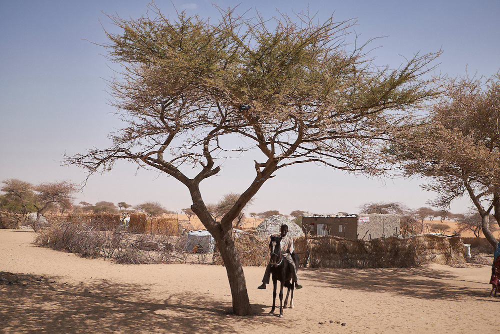 A boy sits on a horse in the village of Guidan Kaji near the border with Nigeria on the outskirts of Diffa, Niger on February 13, 2016. Displaced people from Niger and Nigeria are sheltering in the village after fleeing at the nearby border. Many of the families had witnessed attacks by Boko Haram in their villages or had fled because of other villages around them being attacked. Caritas undertook a distribution of sleeping covers, mosquito nets, pots and money transfers.