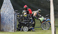 Derek Wegener, at left, fires his paintball gun from behind a barrier with help from Bill Vaughan while Ed Dykshoorn Jr. of the War Hounds paintball team pushes Evan Sugrue in his wheelchair at the Montgomery Sporting Goods paintball fields in the Town of Wallkill on Saturday, Sept. 21, 2013.