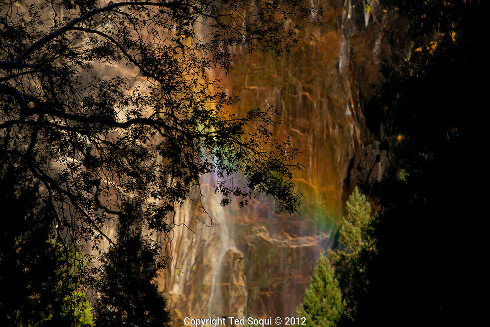A rainbow forms at the bottom park of Bridalveil falls..The autumn season in Yosemite National Park. Leaves and grasses all around the park are changing to their fall colors, and rain and snow are beginning to fall.