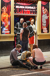 © Licensed to London News Pictures . Manchester , UK . 05/04/2015 . A man and a woman watch over a woman who is slumped forward on the edge of a pavement on Sackville Street , in Manchester City Centre . Revellers on a Saturday night out during the Easter Bank Holiday weekend . Photo credit : Joel Goodman/LNP