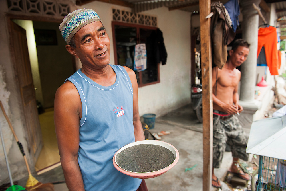 Darman (53 years old) is a miner since 22 years. He earns 6 euros a day. Here with the tin he found on 1 day. <br /> Bangka Island (Indonesia) is devastated by illegal tin mines. The demand for tin has increased due to its use in smart phones and tablets.<br /> <br /> Darman (53 ans). Mineur depuis 22 ans. Gagne 6 euro par jour. <br /> L'&icirc;le de Bangka (Indon&eacute;sie) est d&eacute;vast&eacute;e par des mines d'&eacute;tain sauvages. la demande de l'&eacute;tain a explos&eacute; &agrave; cause de son utilisation dans les smartphones et tablettes