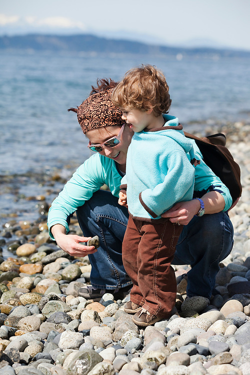 Mother and toddler boy exploring a rocky beach in Lincoln Park, West Seattle, WA USA
