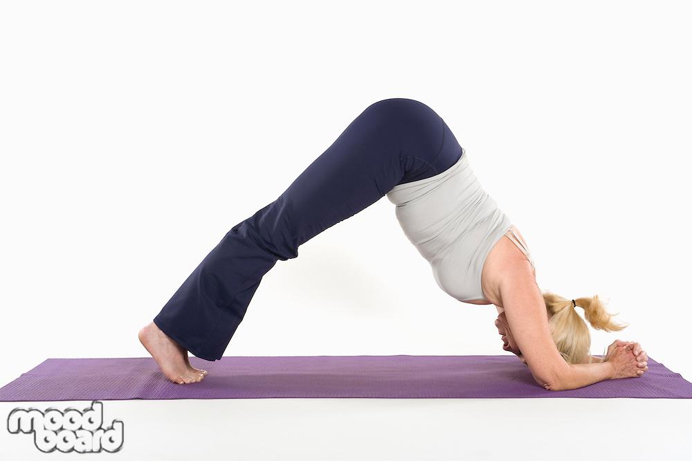 Mature woman doing an expert yoga exercise