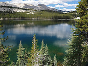 Tenaya Lake's crystal-clear water deepens in hue from emerald to sapphire, ringed by tall pines and white granite, one of the finest sub-alpine lakes in America's Yosemite National Park, California.  Horizontal landscape.
