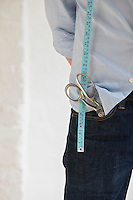 Tailor with scissors in pocket and measuring tape standing indoors mid section close up