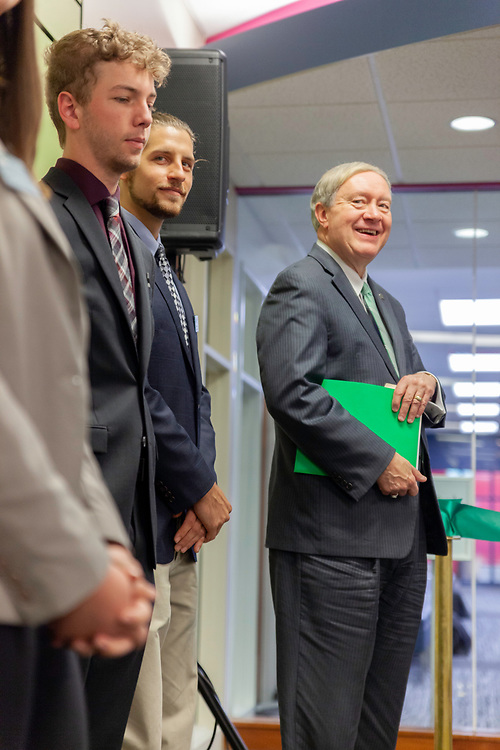 (Left to right) Ben Bowald, a senior in management information systems; Drew Stroud, a senior in mechanical engineering; and Duane Nellis, Ohio University president; listen to David Pidwell, national trustee, speak at the grand opening and ribbon cutting for the new CoLab, October 18, 2018. (Photo by Stephen Zenner/Ohio University Libraries)