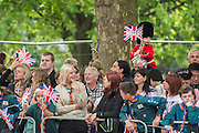 A young Guardsman waves a flags and salutes - Queens 90th birthday was celebrated by the tradition Trooping the Colour as well as a flotilla on the river Thames.