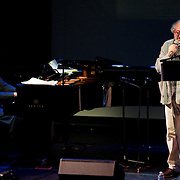 "April 9, 2011 - Manhattan, NY : American composer Philip Glass, left, performs on the piano as Hal Willner recites poetry by Allen Ginsberg during the Japan Society's 12-hour-long special ""Concert For Japan"" charity event on Saturday.  (This was taken during the 1-2:20pm Gala Block)... CREDIT: Karsten Moran for The New York Times."