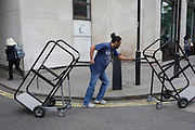 A man struggles to push and pull two loading cages along a central London street, on 4th June 2019, in London, England.