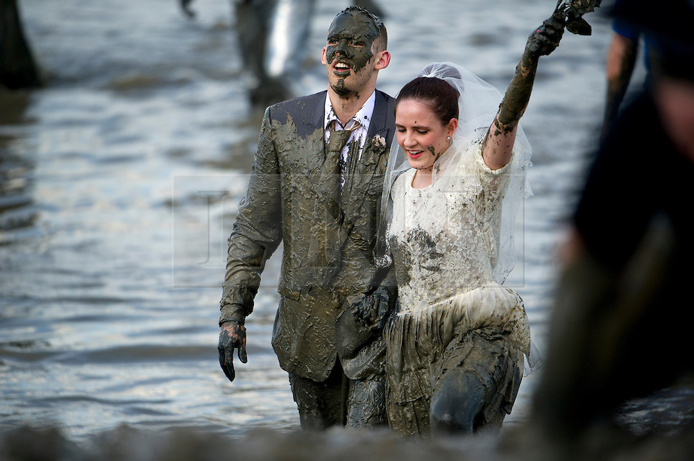 © London News Pictures. 05/05/2013. Maldon, UK. A couple dressed as a bride and groom take part in the Maldon Mud Race in Maldon, Essex on May 05, 2013. The race originated in 1973 and involves competitors racing around a course on the mudbanks of the river Blackwater at low tide. Photo credit: Ben Cawthra/LNP.