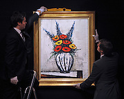 © Licensed to London News Pictures. 02/02/2012, London, UK. Two gallery assistants hang Bernard Buffet's 'Delphiniums et pavots'. The painting is expected to fetch 30,000-50,000GBP.  Photo call at Bonhams, London for Impressionist and Modern Art Auction preview..  Photo credit : Stephen Simpson/LNP