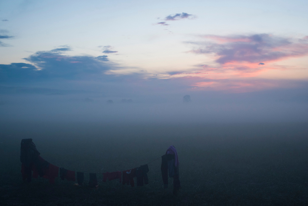 Clothes, wet from persistent rains, hang on a line to dry at dawn in a refugee camp on the Macedonian (FYROM) border on March 11, 2016 in Idomeni, Greece.