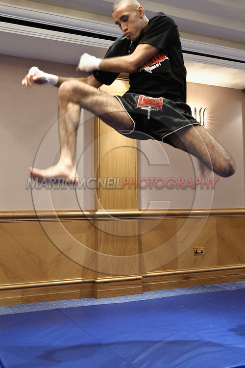 BIRMINGHAM, ENGLAND, NOVEMBER 2, 2011: Terry Etim performs a flying knee strike at the media open work-out sessions inside the Hilton Hotel on November 2, 2011.