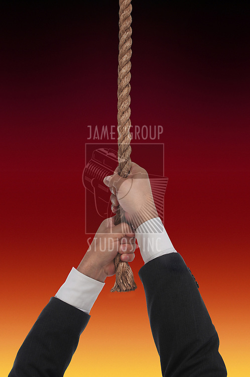 man hanging at end of his rope over fire