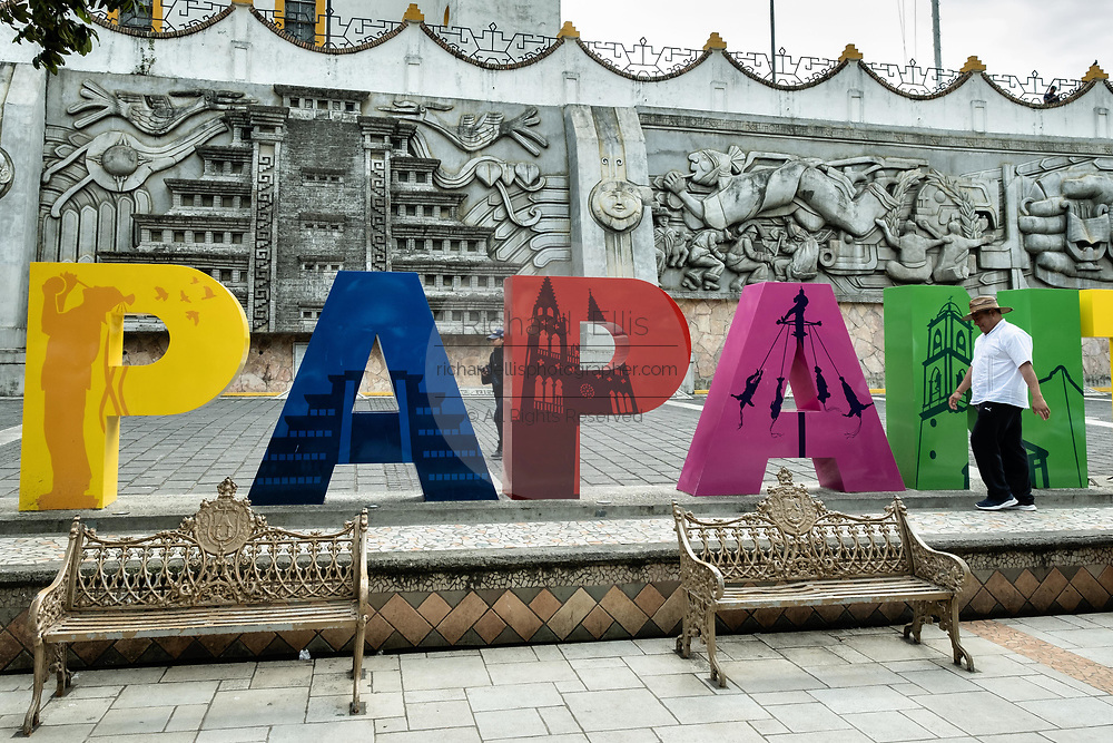 A man walks past the city sign past the sculpture Evolution of the Totonac culture by Teodoro Cano Garcia, in the Plaza Central Israel Tellez Park in Papantla, Veracruz, Mexico.