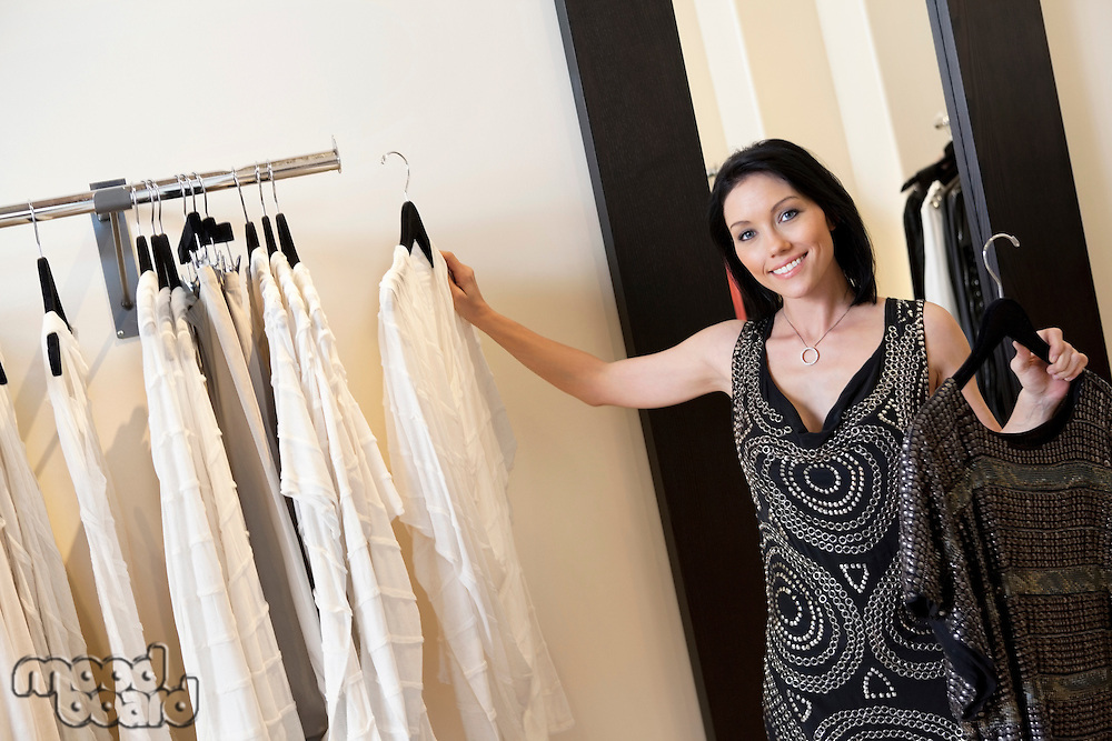 Portrait of a beautiful mid adult woman selecting dress from rack in fashion boutique