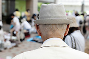 elderly person with hat seen from the back