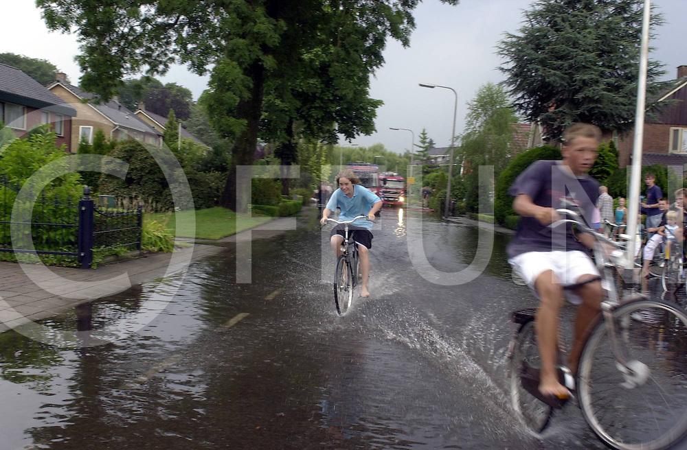 060723,raalte,nederland,<br /> wateroverlast in de straten van raalte naar hoosbui, kinderen vermaken zich wel,<br /> fotografie frank uijlenbroek&copy;2006 michiel van de velde