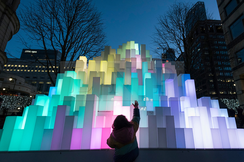 © Licensed to London News Pictures. 18/01/2020. LONDON, UK. A young visitor interacts with Mountain of Light by Angus Muir Design at the sixth Winter Lights festival in Canary Wharf.  25 light art and interactive installations by international artists are on display for the public to enjoy until 25 January 2020.  Photo credit: Stephen Chung/LNP