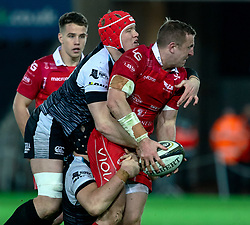 Hadleigh Parkes of Scarlets under pressure from  Sam Cross of Ospreys<br /> <br /> Photographer Simon King/Replay Images<br /> <br /> Guinness PRO14 Round 11 - Ospreys v Scarlets - Saturday 22nd December 2018 - Liberty Stadium - Swansea<br /> <br /> World Copyright © Replay Images . All rights reserved. info@replayimages.co.uk - http://replayimages.co.uk