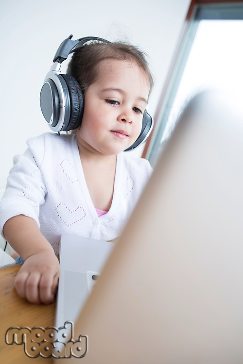 Little girl wearing headphones while looking at laptop at table in house