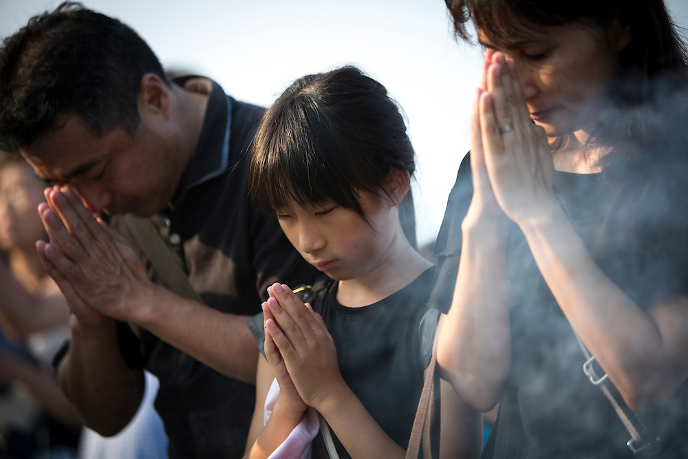 """HIROSHIMA, JAPAN - AUGUST 6 : Visitors lays flowers and pray for the atomic bomb victims in front of the cenotaph during the 71st anniversary of the atomic bombing on Hiroshima at Hiroshima Peace Memorial Park in Hiroshima, western Japan, Saturday, August 6, 2016. Japan marked the 71st anniversary of the atomic bombing on Hiroshima. On August 6, 1945, during World War II, the United States dropped a uranium gun-type atomic bomb named """"Little Boy"""" on the city of Hiroshima which instantly killed an estimated 80,000 people, tens of thousands more would later die of radiation exposure. Three days later, a second American B-29 bomber dropped a plutonium implosion-type bomb """"Fat Man"""" on Nagasaki, killing an estimated 40,000 people.  (Photo: Richard Atrero de Guzman/NURPhoto)"""