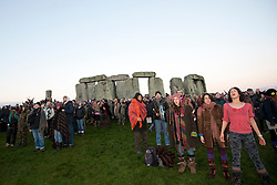 © Licensed to London News Pictures. 21/12/2012. Stone Henge, Wiltshire. People celebrate Winter Solstice at Stone Henge. Stone Henge was opened to the public this morning so people could celebrate the Solstice and watch the sun rise from amongst the stones. Many people believe that Winter Solstice 2012 will be the end of the world Photo credit : David Mirzoeff/LNP