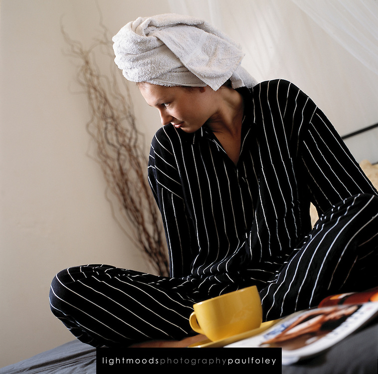 Young woman relaxing in bedroom with coffee and magazine