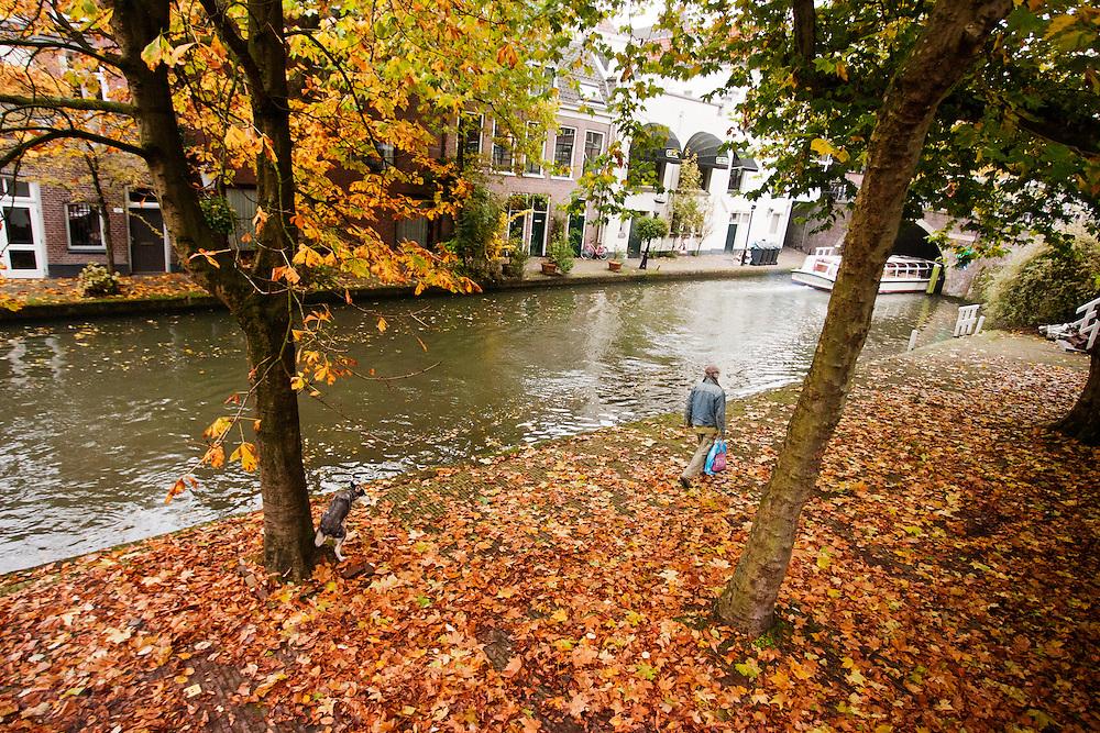 Een man loopt met zijn hond, die een behoefte doet, langs de gracht van Utrecht.<br /> <br /> A man is walking with his dog at the canals of Utrecht