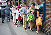 © Licensed to London News Pictures. 19/06/2014. Ascot, UK. People queue for cash.  Day three, Ladies Day, at Royal Ascot 19th June 2014. Royal Ascot has established itself as a national institution and the centrepiece of the British social calendar as well as being a stage for the best racehorses in the world. Photo credit : Stephen Simpson/LNP