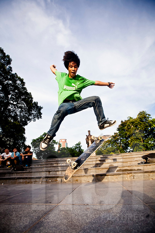 Young Vietnamese teenager performs skateboarding tricks in the public square by Ly Thai To statue near Hoan Kiem Lake, Hanoi, Vietnam, Southeast Asia