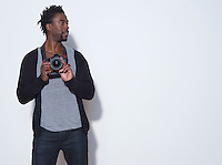 Mid adult (30-35 years) photographer holding camera studio shot