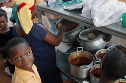 Ghana, Accra, Kokomlemle, 2007. Rice and sauce vendors supply the students at Kwameh Nkrumah Memorial School with breakfast. Most children will go home for lunch.