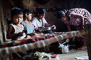 (name changed) Neelam Bharadwaj, 16, (second from right) is preparing some rice for cooking, while her older sister Sanju, 29, (right) is preparing a pot with water, inside their home in Rajbhar village, located around 20 kilometres away from Varanasi, in Uttar Pradesh, India. Sanju's children, Payel, 5, (second from left) and Prince Kumar, 3, (left) are sitting nearby. Neelam was raped when she was 13 years old. After walking to a local shop on the main road neighbouring her village, she was forcibly picked up by two men. While one of them was raping her in the bushes, the other watched out. After some time, she managed to free herself and run away, hiding under a bridge in cold dirty water for several hours. When she returned home in the morning, the family was too afraid to go to the police, but activist Mangla Parsad, 34, from PVCHR, convinced the family to take the right action. The police initially insulted and threatened the family for bringing the facts up, but filed the official case (FIR) nevertheless. The rape was not mentioned in the file due to an inaccurate and superficial medical record that did not, in fact, mention it. Because of social shame facing by victims of rape in India, the family agreed to wed Neelam to an older man, with help of an agent. After the marriage, her husband raped her again for a whole month before she decided to return home with her family. Neelam's father works in the metal industry in Mumbai and manages to send around 2-3000 INR every month. He only visits the family once in a year. Neelam goes to school and she is studying in 11th Class Standard. She is interested in doing BA in Arts after completing her high school 12th final year.
