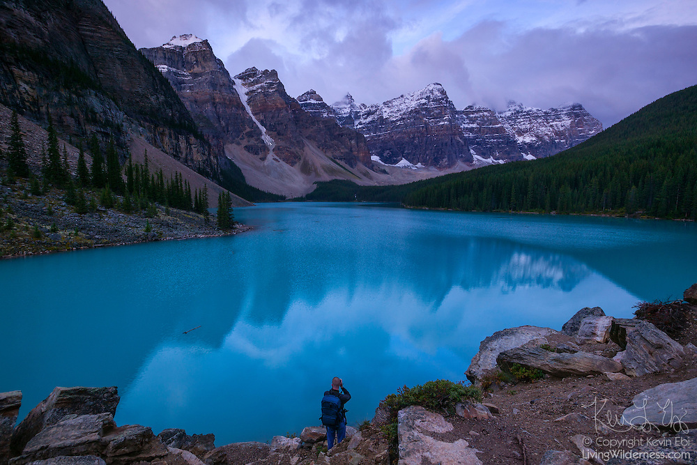 A man photographs the morning light on the mountains surrounding Moraine Lake in Banff National Park, Alberta, Canada.