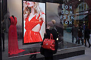 Blonde model shown on a video loop in a central London shop window, in the run-up to London Fashion Week.
