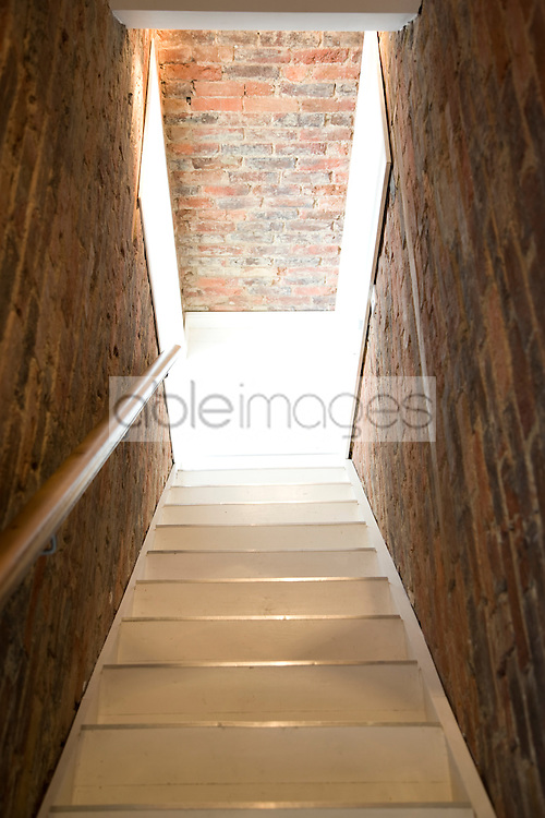 Empty staircase with hand rail and brick walls