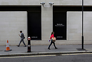 Londoners walk beneath two CCTV cameras in the City of London, one of the most-watched  on 11th August, 2017, in London, England. According to 2011 figures, there are 420,000 CCTV cameras in London.
