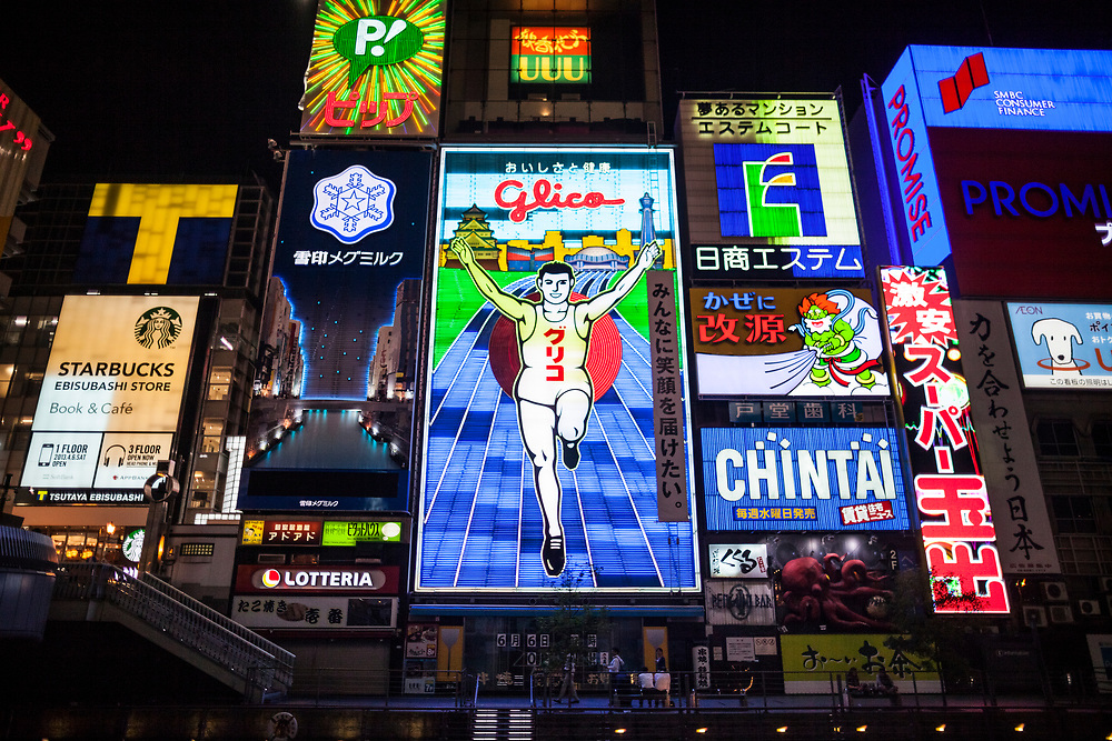 The famous running man neon sign at night along the Dotonbori river in Osaka, Japan.