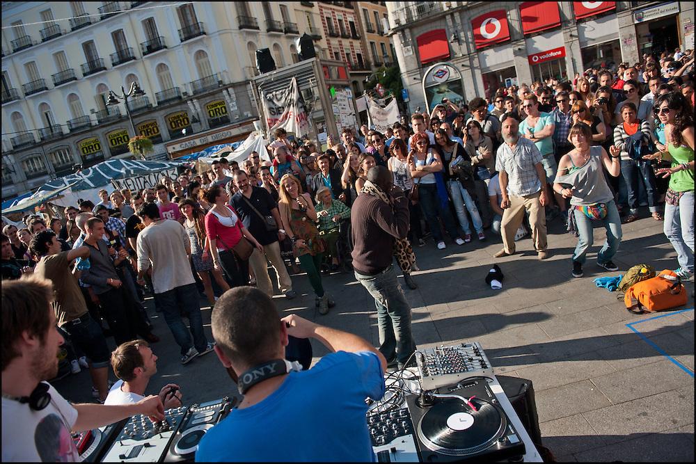 """Deux Dj benevoles viennent mettre de l'ambiance sur le camp. // Le mouvement spontane du """"15 M"""" (15 mai) compose de citoyens espagnols campe depuis 2 semaines sur la place Puerta Del Sol avec pour revendication la construction d'une democratie nouvelle. Organise en commission les citoyens prennent la parole lors d'assemblee ouverte a tous - Place Puerta Del Sol à Madrid le Juin 2011. ©Benjamin Girette/IP3Press"""