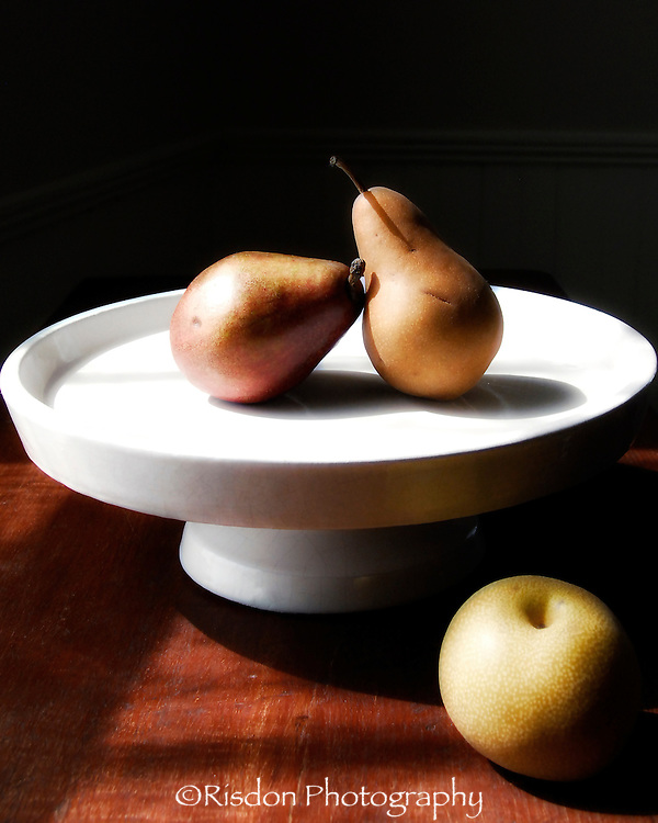 still life pears on white plate with apple on wooden table