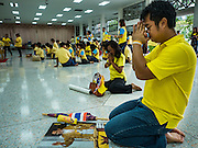 05 DECEMBER 2015 - BANGKOK, THAILAND:  A man prays for the King in the lobby at Siriraj Hospital on the 88th birthday of Bhumibol Adulyadej, the King of Thailand. Hundreds of people crowded into the plaza hoping to catch a glimpse of the revered Monarch. The King has lived at Siriraj Hospital off and on for more than four years.    PHOTO BY JACK KURTZ