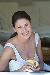 Brunette woman enjoying a morning cup of coffee