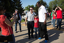 Tammy O'Neill, left, takes a photo of her son Shane, center, with UofL Men's head basketball coach Rick Pitino and UofL center Gorgui Dieng after workouts Wednesday, May 01, 2013 at Churchill Downs in Louisville. The O'Neills are related to Doug O'Neill trainer of Derby 139 hopeful Goldencents. Pitino is part owner of the horse as well. Photo by Jonathan Palmer